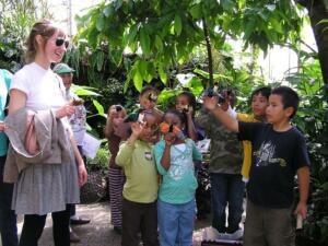 Malcolm X school group visiting the Tropical House with pollinator puppets in front of cacao tree.